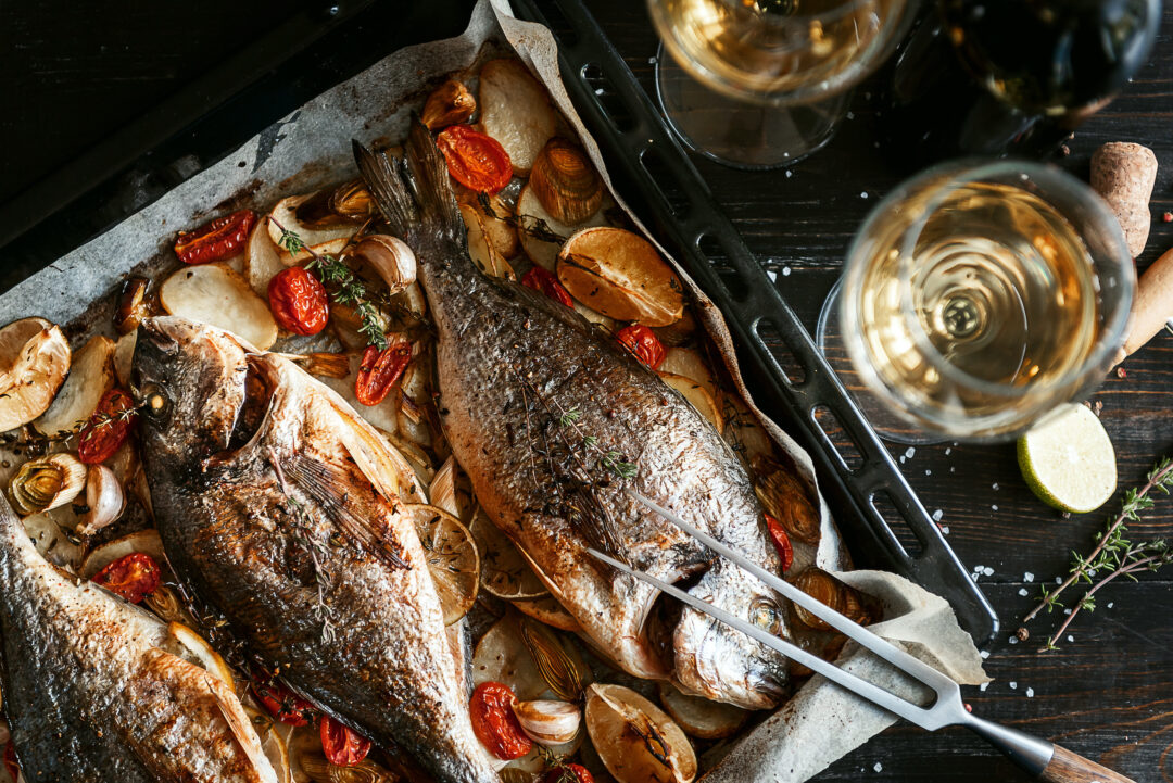 overhead of fish fillets on tray with glasses of white wine