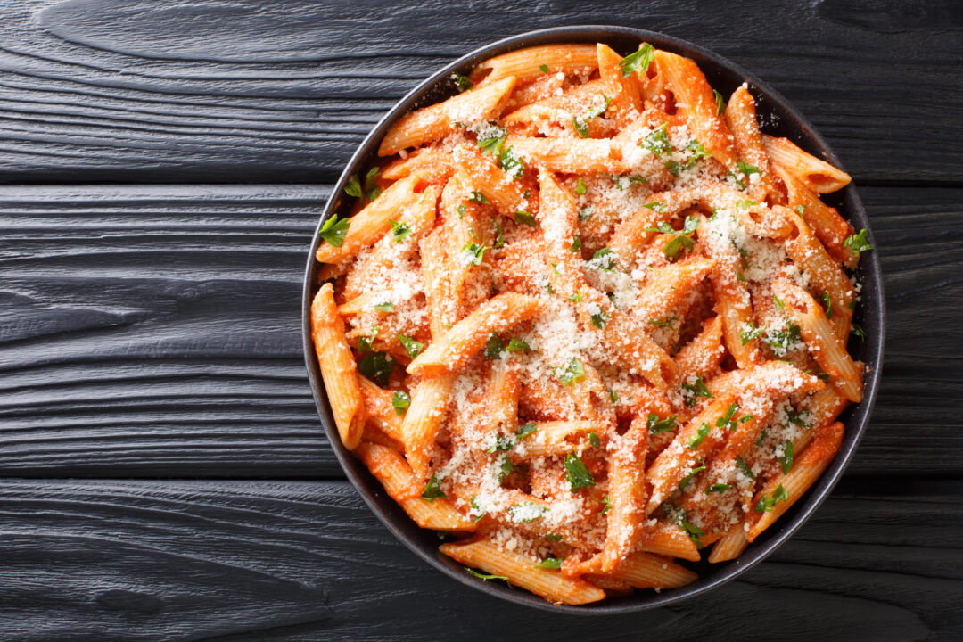 overhead of pasta in bowl with tomato sauce and cheese