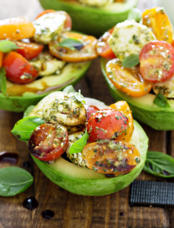 Overhead of avocados stuffed with tomatoes, mozzarella and basil on wood board
