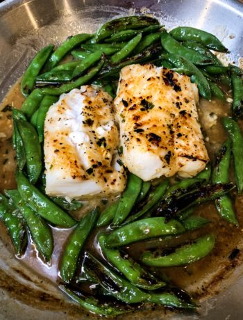 overhead of broiled miso-butter cod with snap peas in a skillet