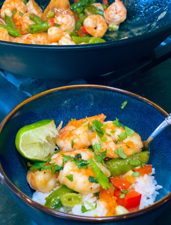 overhead of garlic honey shrimp over white rice, topped with cilantro and lime