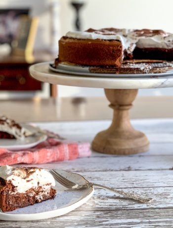 Cloud cake on a raised marble cake stand, with a piece of cake on a plate topped with whipped cream
