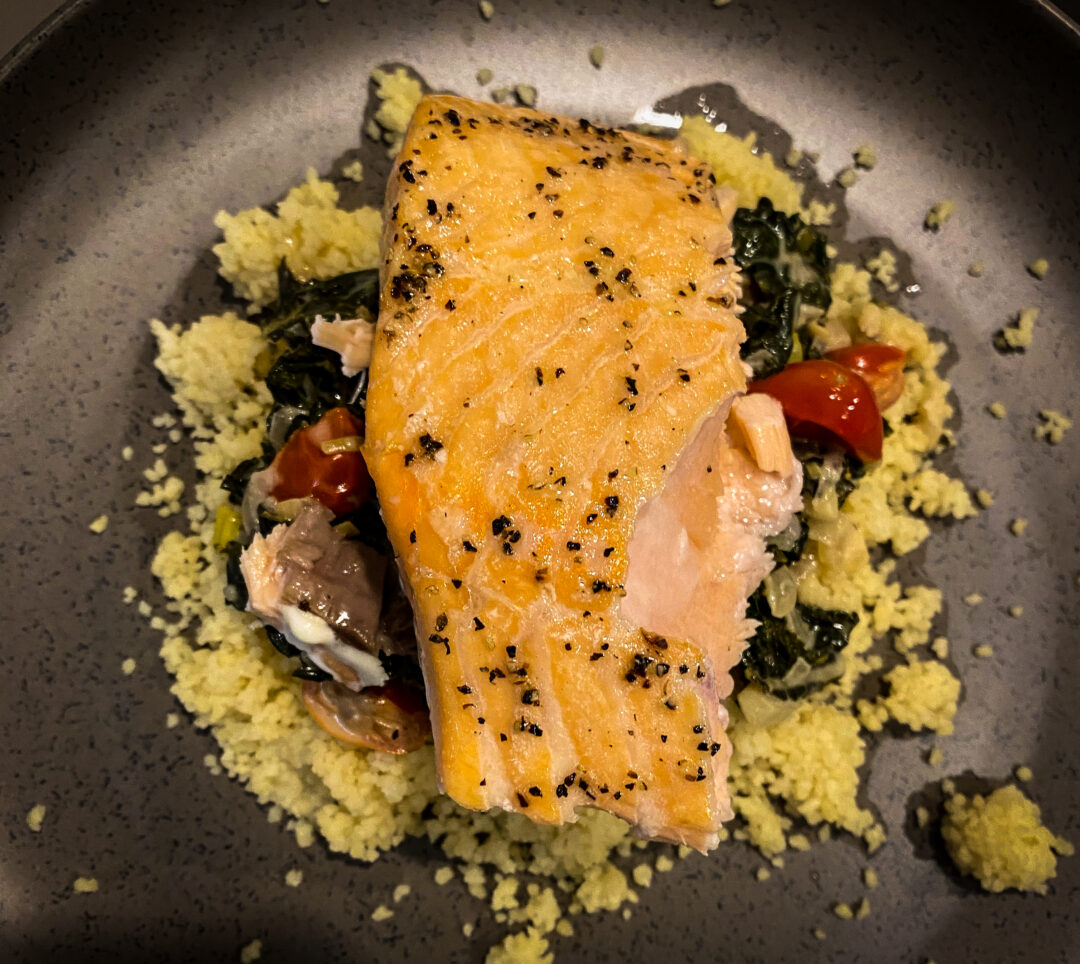 close up overhead view of salmon over couscous on brown plate