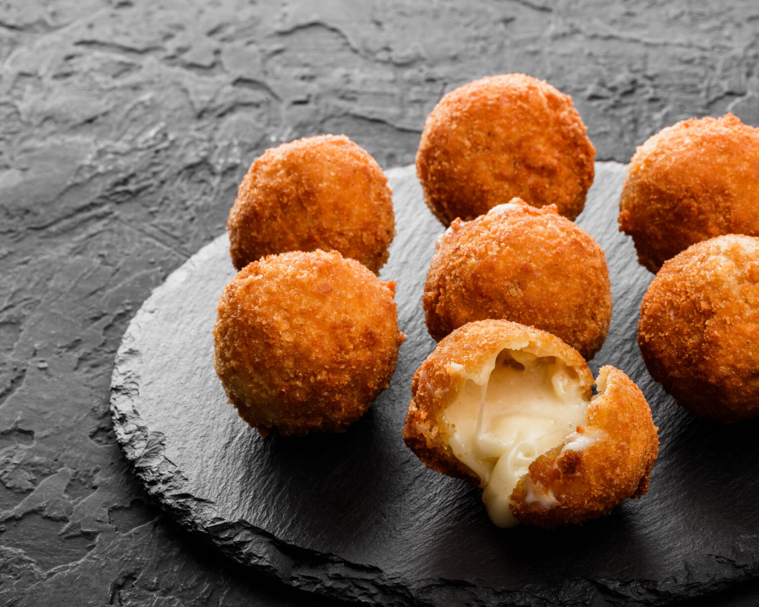 Fried potato cheese balls or croquettes with spices on black plate over dark stone background. Unhealthy food, top view.