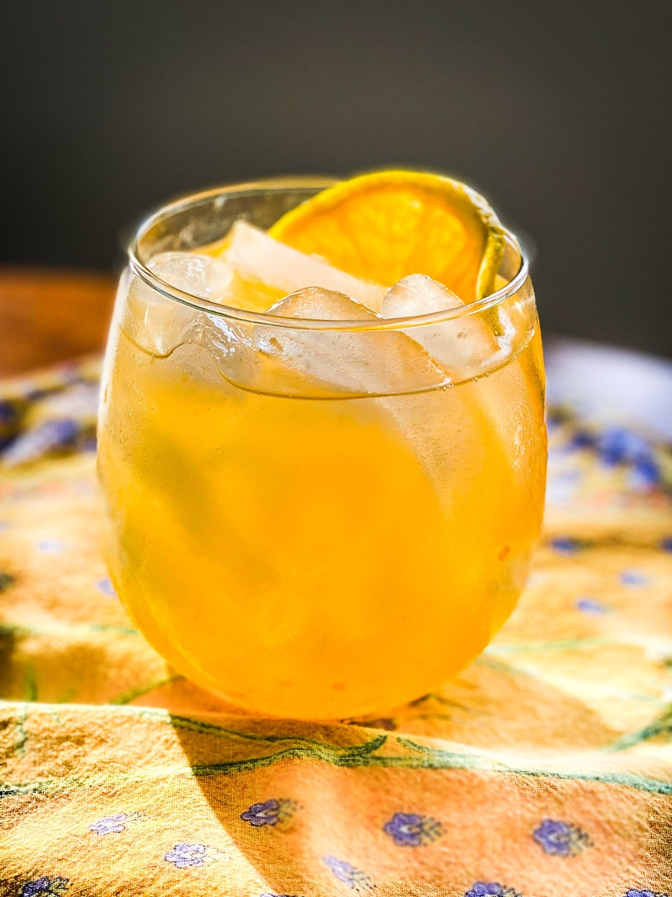 drink in a small glass on yellow tablecloth with orange slice