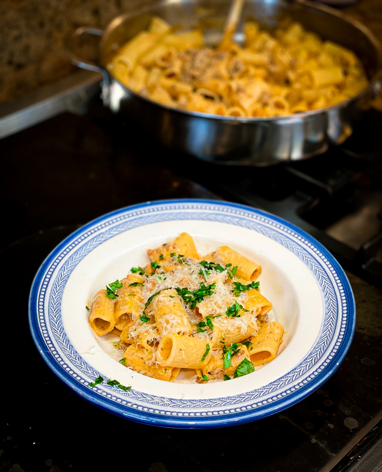 overhead shot of pasta with cheese in blue dish and pot of pasta in background