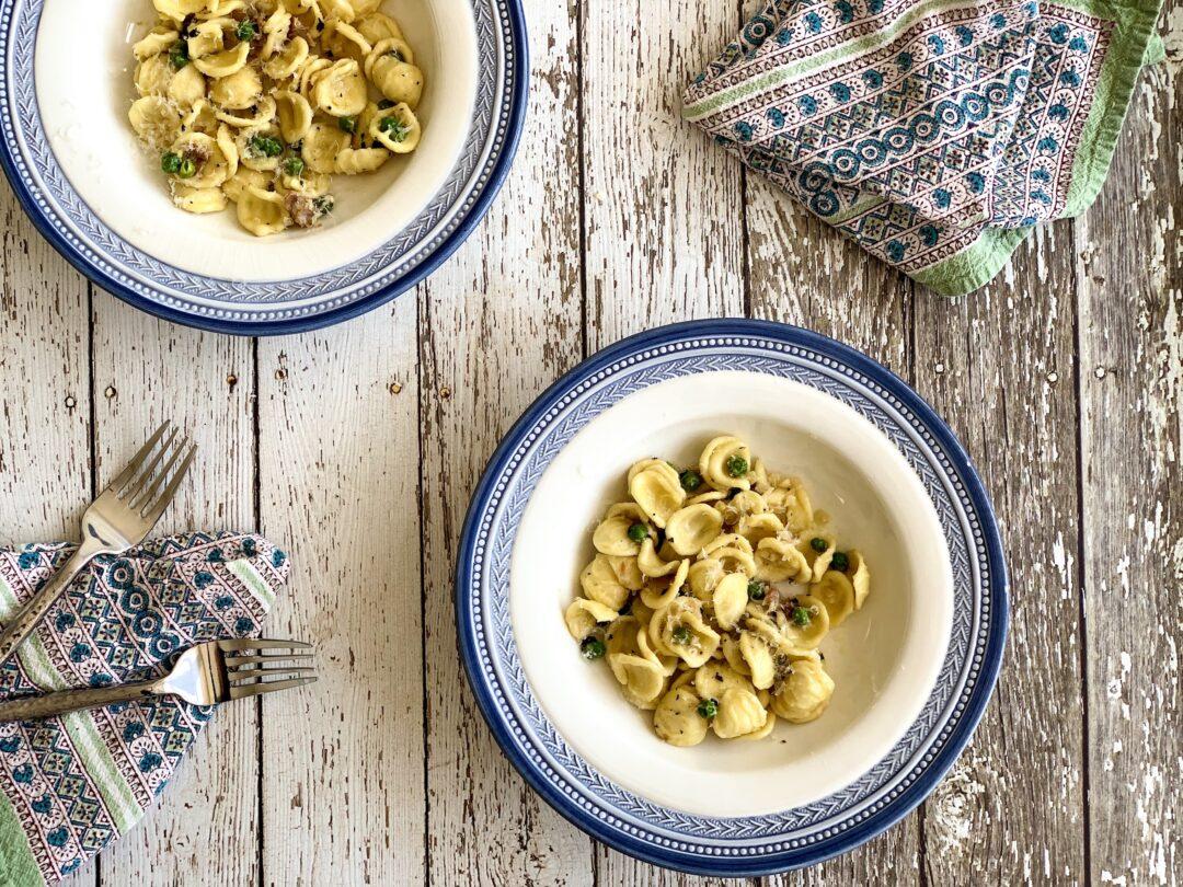 overhead of orecchiette pasta with peas and prosciutto in a bowl